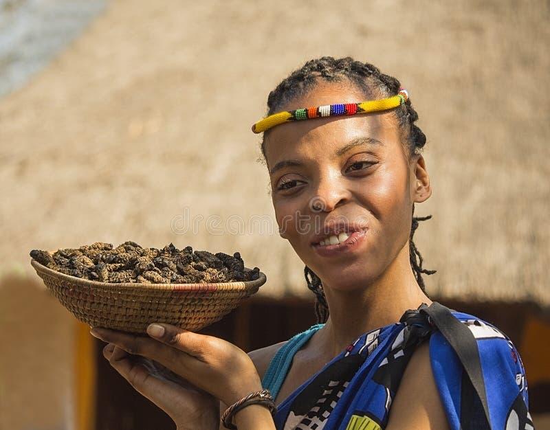 Lächelnde Bantu Nation der jungen Frau, die essbare Gleiskettenfahrzeuge für Abendessen dient Berühmter Kanonkop Weinberg nahe ma lizenzfreie stockfotografie