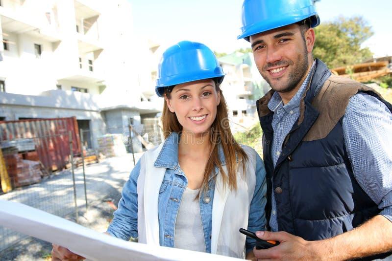 Lächelnde Bauarbeiter auf Standort lizenzfreie stockbilder