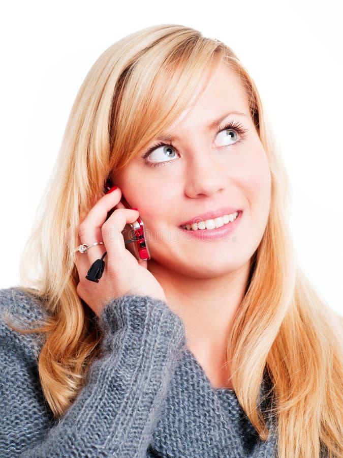 Lächelnde blonde Frau, die durch Telefon benennt stockbilder
