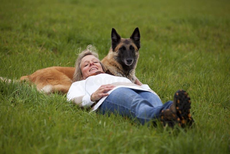 Lächelnde blonde Frau, die mit ihrem Hund entspannt lizenzfreies stockbild