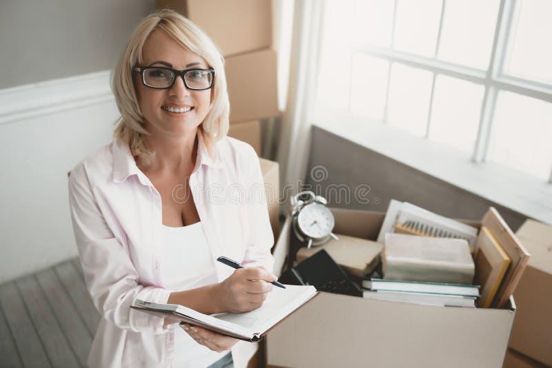 Lächelnde blonde Frau mit Gläsern mit Notizbuch stockbild
