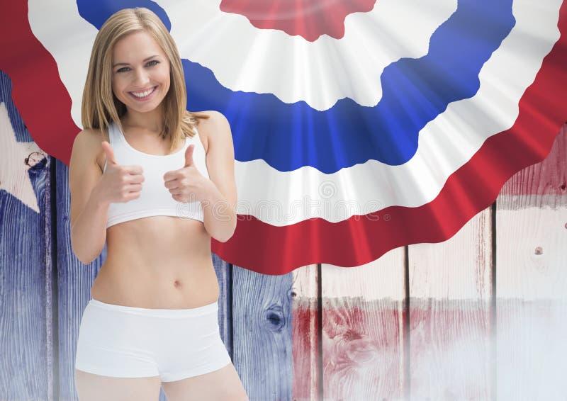 Lächelnde blonde Frauendaumen oben gegen amerikanische Flagge lizenzfreies stockbild