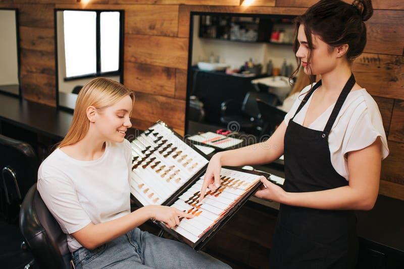 Lächelnde blonde junge Frau und Friseur, die Haarfarbe von der Palette vor der Färbung im Schönheitssalon wählen schönheit lizenzfreies stockfoto