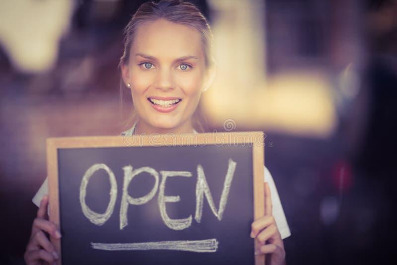 Lächelnde blonde Kellnerin, die Tafel mit offenem Zeichen zeigt lizenzfreies stockfoto