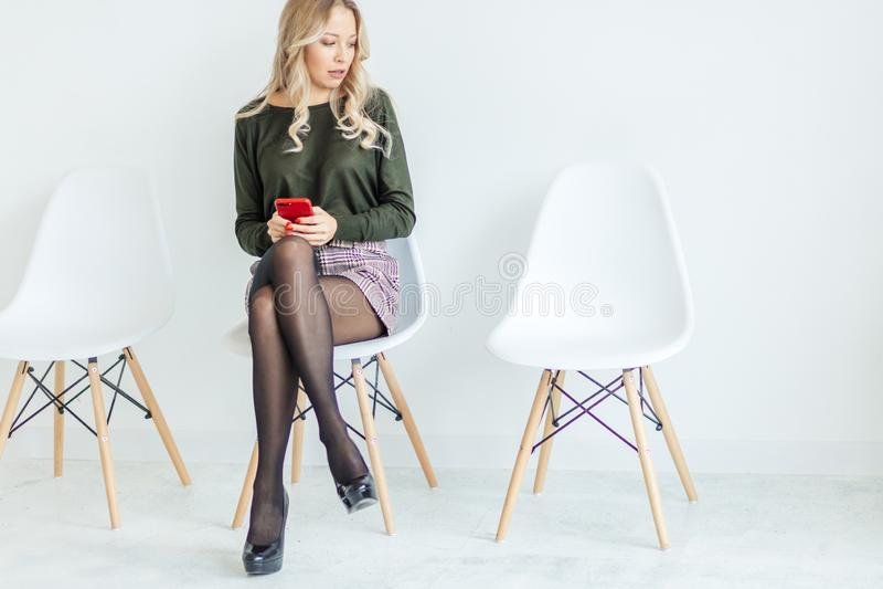 Lächelnde Blondine, die auf Bürostuhl sitzen Junger Assistent am Arbeitsplatz lizenzfreies stockbild