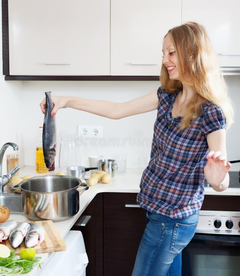 Lächelnde Blondine, die Fische kochen stockfoto
