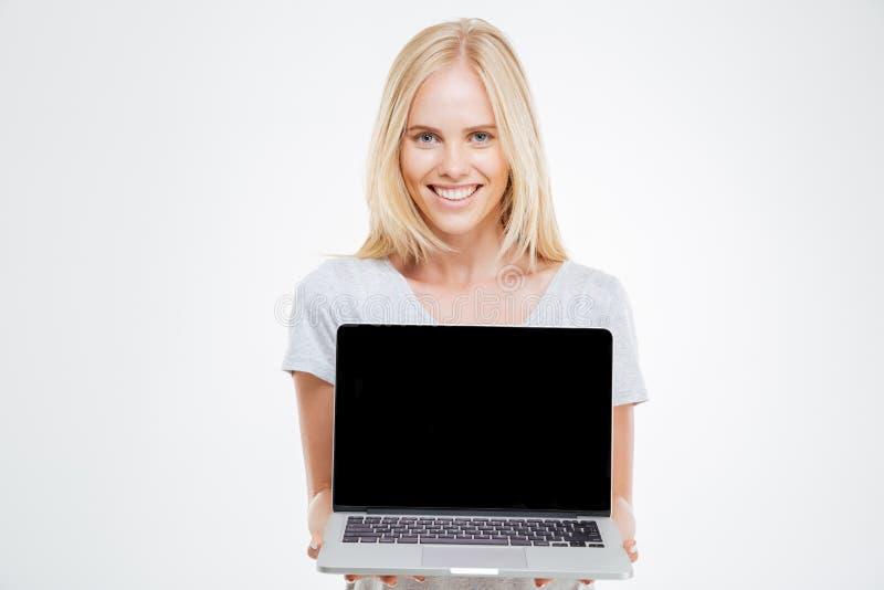 Lächelnde Blondine, die leeren Laptop-Computer Schirm zeigen lizenzfreie stockbilder