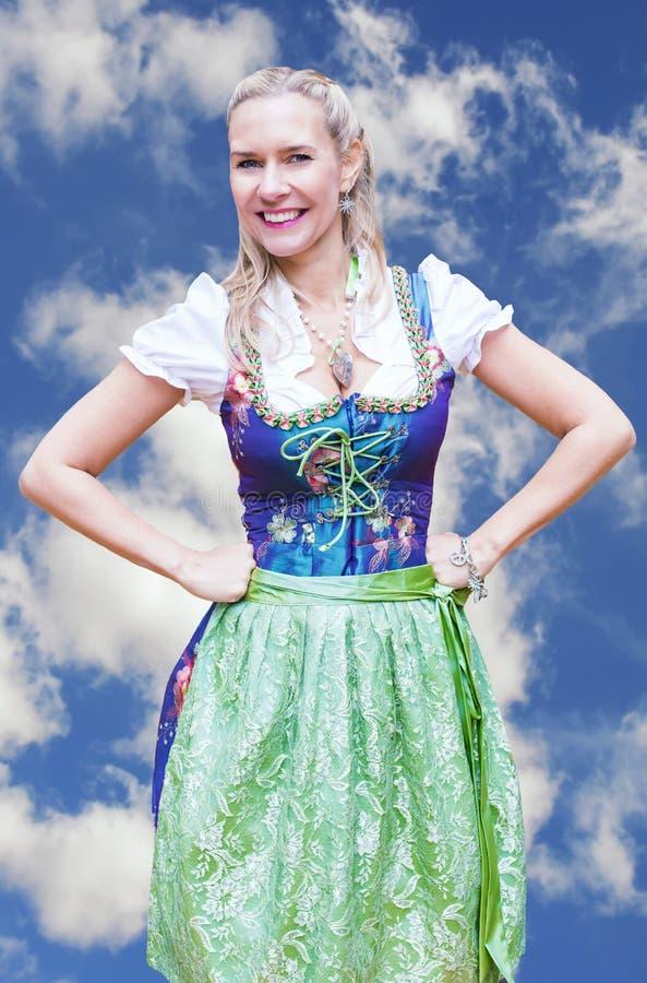 Lächelnde Blondine im Dirndl vor blauem Himmel lizenzfreies stockfoto
