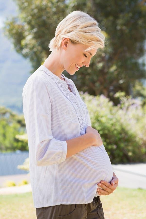 Lächelnde Blondine schwanger mit den Händen auf seinem Bauch lizenzfreies stockbild
