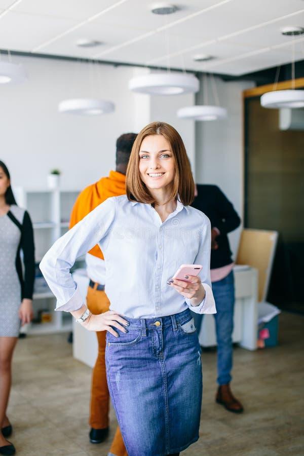 Lächelnde braunhaarige Frau wirft zur Kamera auf stockfotos