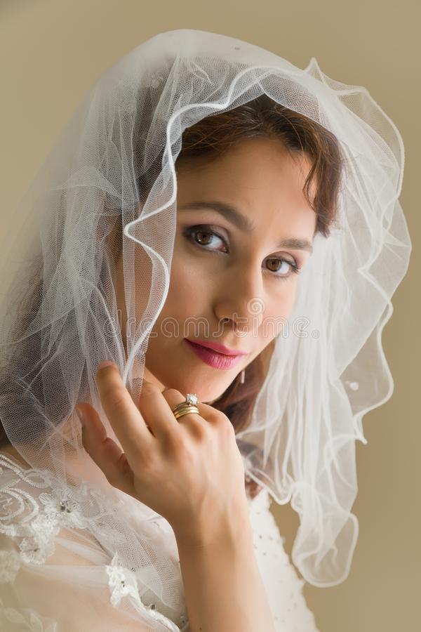 L?chelnde Braut, die mit ihrem Schleier spielt lizenzfreie stockfotografie