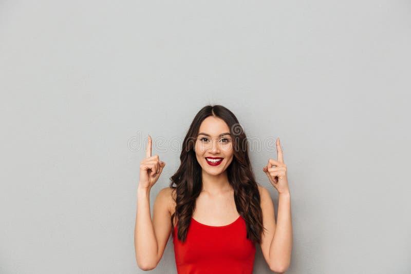 Lächelnde Brunettefrau in der zufälligen Kleidung oben zeigend stockfotos