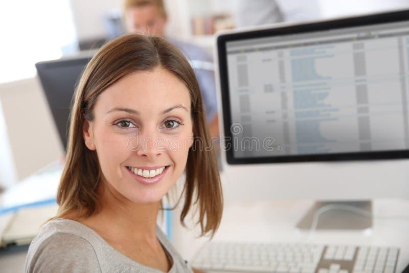 Lächelnde Brunettefrau im Büro stockfoto