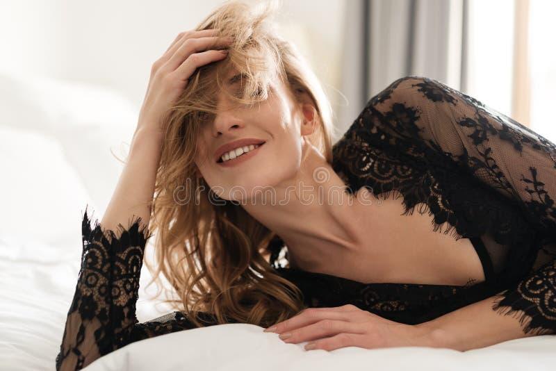 Lächelnde Brunettefrau liegt auf Bett zuhause lizenzfreie stockfotos