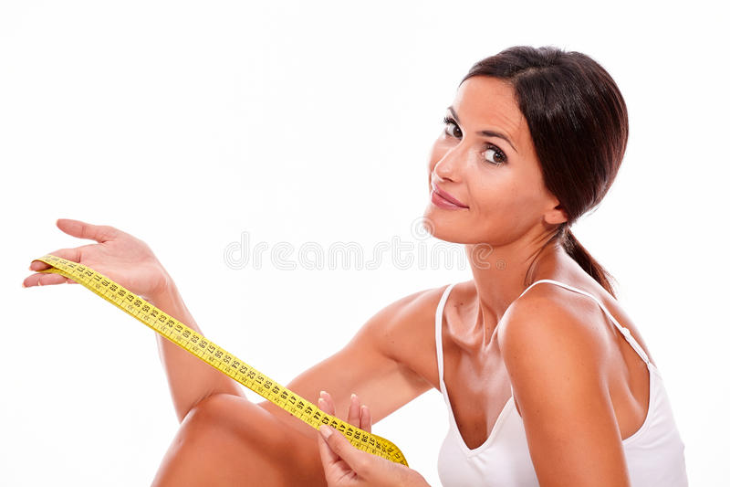 Lächelnde Brunettefrau mit Maßband lizenzfreies stockbild