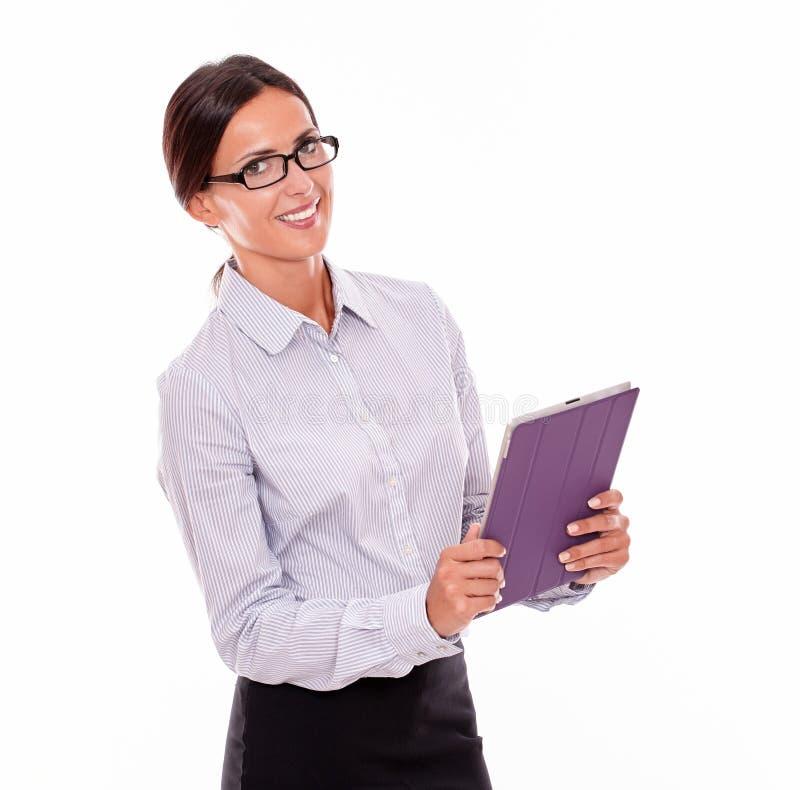 Lächelnde Brunettegeschäftsfrau, die eine Tablette trägt stockbild
