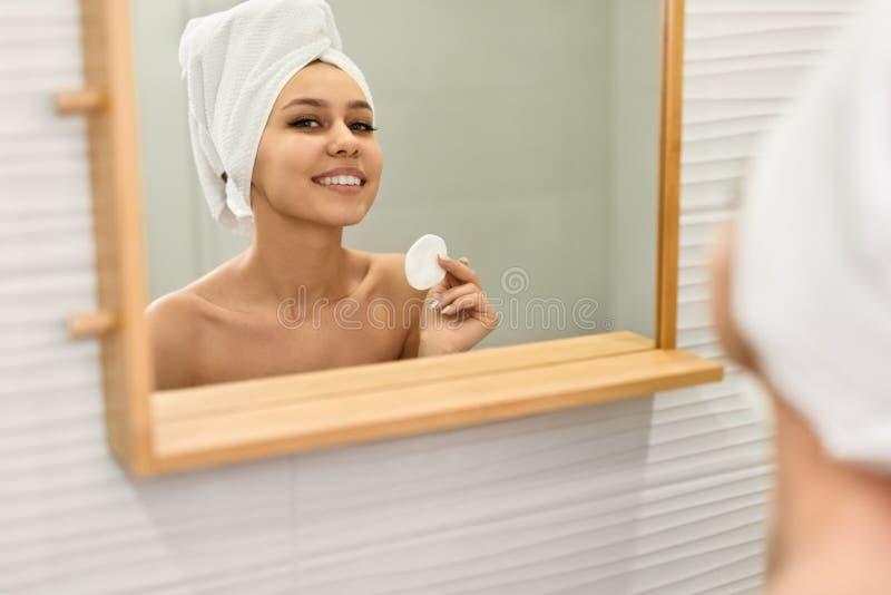 Lächelnde Dame, die skincare Programm nahe Spiegel durchführt stockbild