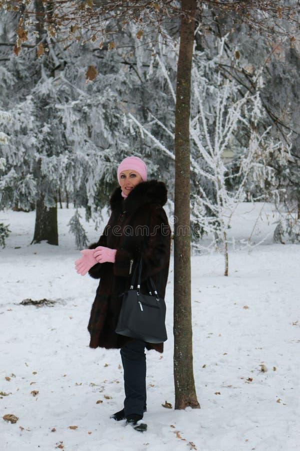 Lächelnde Dame in einem Pelzmantel im Winterwald stockfotografie