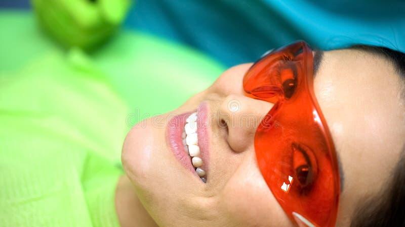 Lächelnde Dame zufrieden gewesen mit Zahnarztprofessionalismus, Zahnheilkunde für abgebrochenen Zahn stockfoto
