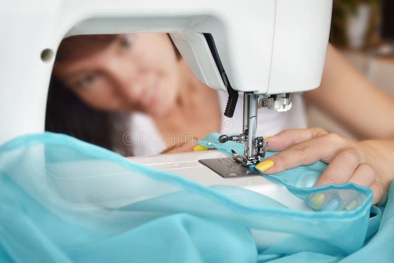 Lächelnde Damenschneiderinfrau näht Kleidung auf Nähmaschine Näherin und ihr Handabschluß oben stockfotografie