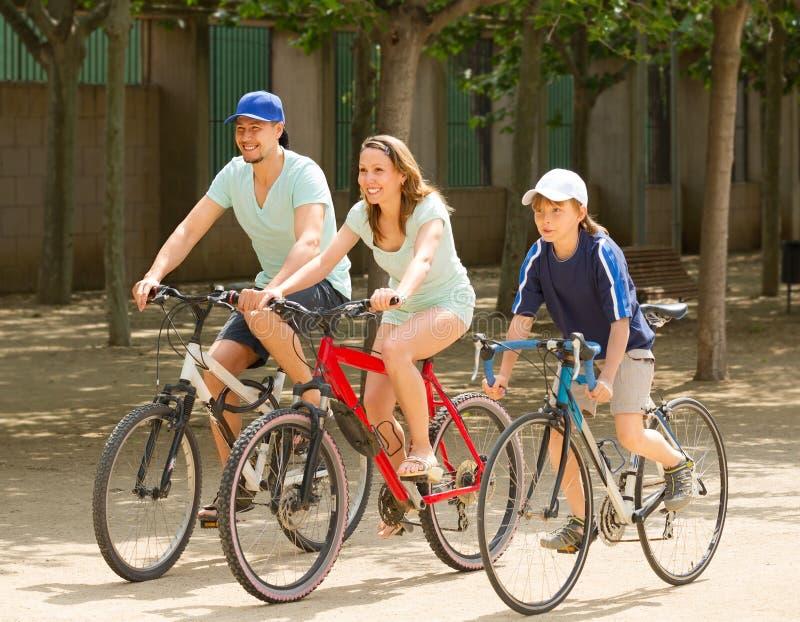 Lächelnde dreiköpfige Familie, die auf Straßenstraße radfährt stockbilder