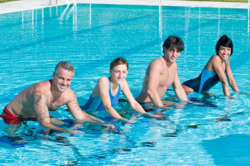 Lächelnde Eignungleute, die im Swimmingpool trainieren lizenzfreies stockbild