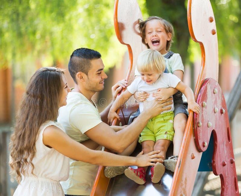 Lächelnde Eltern, die Kindern auf Dia helfen lizenzfreie stockfotografie