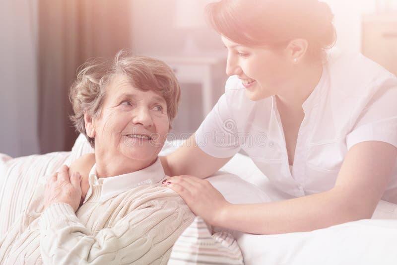 Lächelnde Enkelin, die glückliche Großmutter während der Familiensitzung umarmt lizenzfreie stockbilder