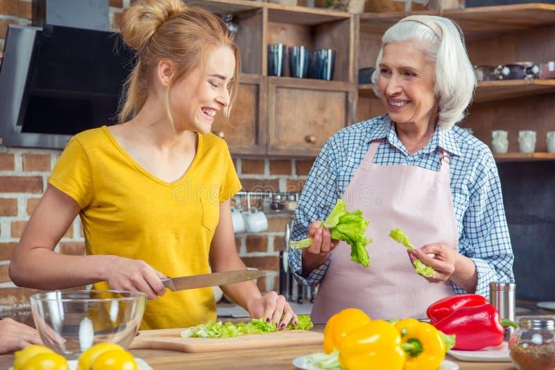 Lächelnde Enkelin und Großmutter, die zusammen kochen stockfoto