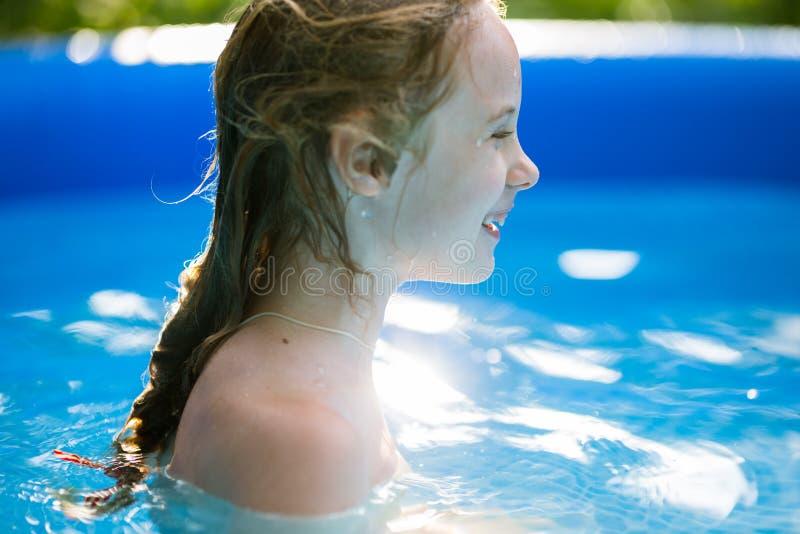 Lächelnde entzückende sieben Jahre alte Mädchen, die Spaß im aufblasbaren Pool spielen und haben lizenzfreie stockbilder