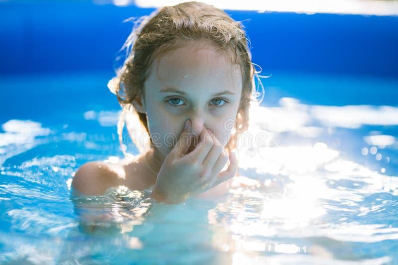 Lächelnde entzückende sieben Jahre alte Mädchen, die Spaß im aufblasbaren Pool spielen und haben stockbild
