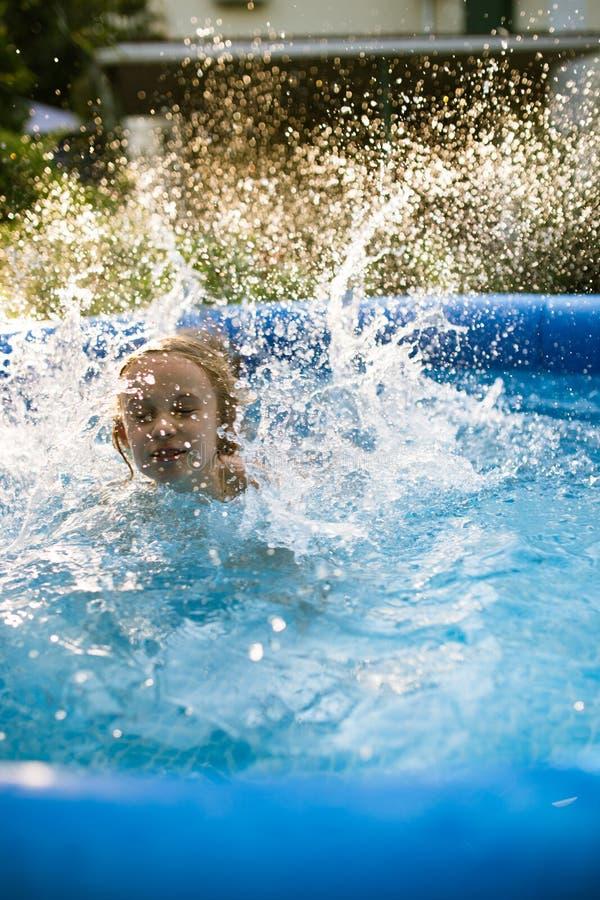 Lächelnde entzückende sieben Jahre alte Mädchen, die Spaß im aufblasbaren Pool spielen und haben lizenzfreies stockfoto