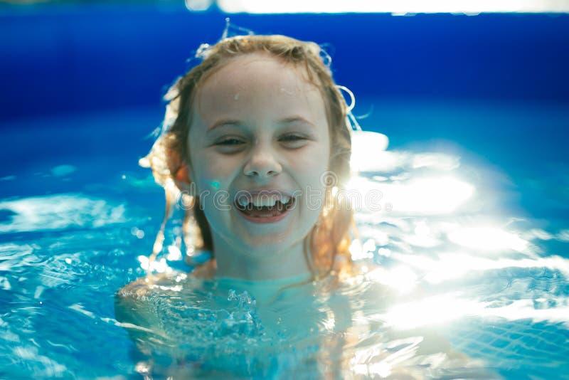 Lächelnde entzückende sieben Jahre alte Mädchen, die Spaß im aufblasbaren Pool spielen und haben lizenzfreie stockfotos