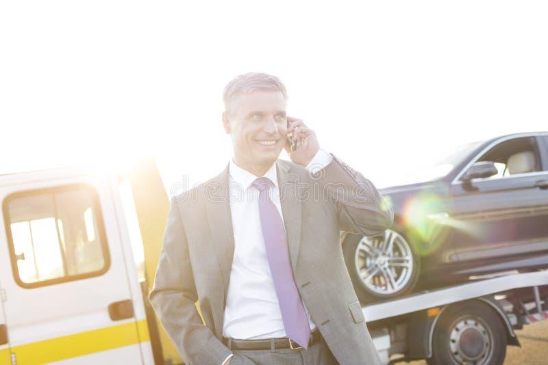 Lächelnde Exekutive, die am Handy während Abschleppwagen aufhebt sein Auto spricht lizenzfreies stockbild