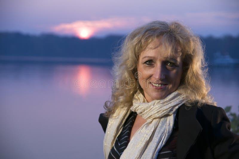 Lächelnde fällige Frau durch See lizenzfreies stockfoto