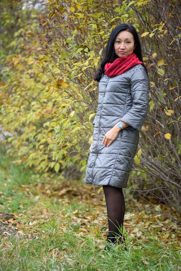 Lächelnde Fallfrau - Herbstporträt der glücklichen asiatischen kaukasischen jungen Frau der reizenden und schönen Mischrasse im W lizenzfreie stockfotos