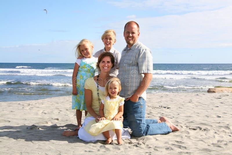 Lächelnde Familie auf dem Strand stockfotografie