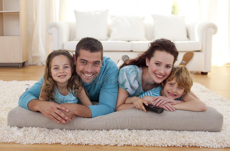Lächelnde Familie auf Fußboden im Wohnzimmer stockfotos