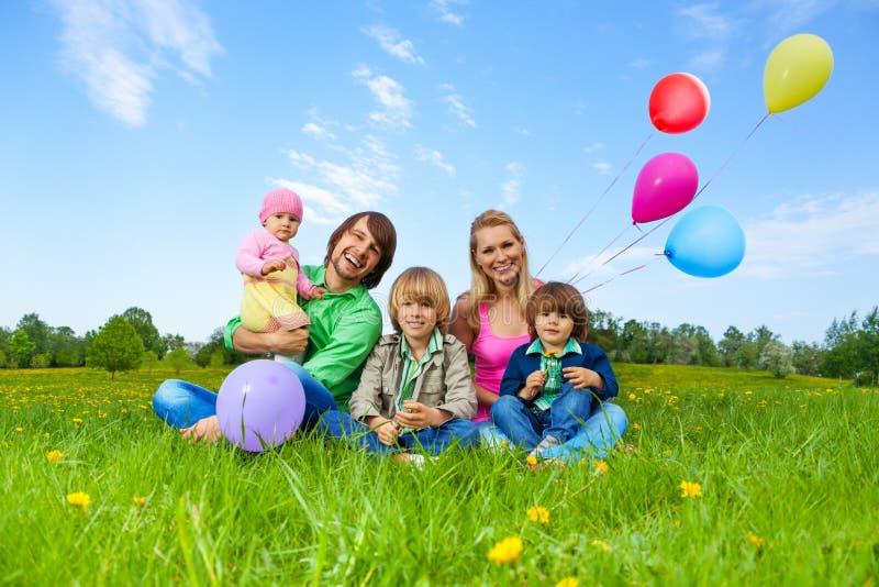 Lächelnde Familie, die auf Gras mit Ballonen sitzt lizenzfreie stockfotos