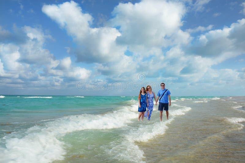 Lächelnde Familie, die auf schönen Strand geht lizenzfreie stockbilder