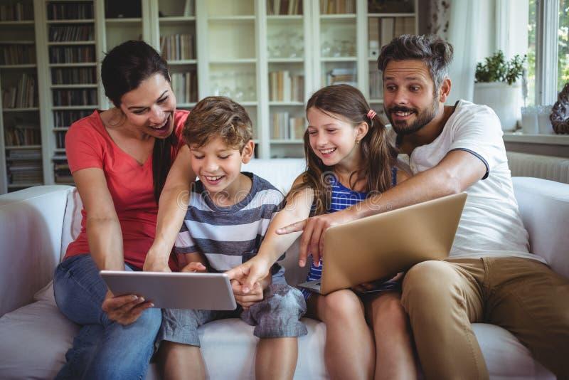 Lächelnde Familie, die auf Sofa sitzt und auf digitale Tablette zeigt stockbild