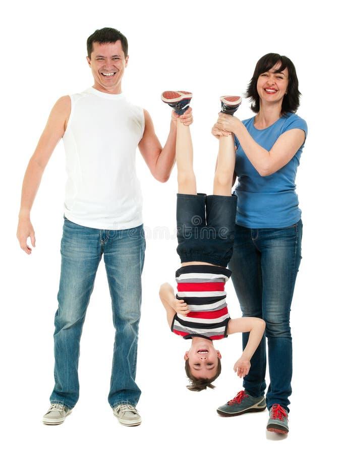 Lächelnde Familie, die den Spaß lokalisiert auf Weiß hat lizenzfreie stockfotos
