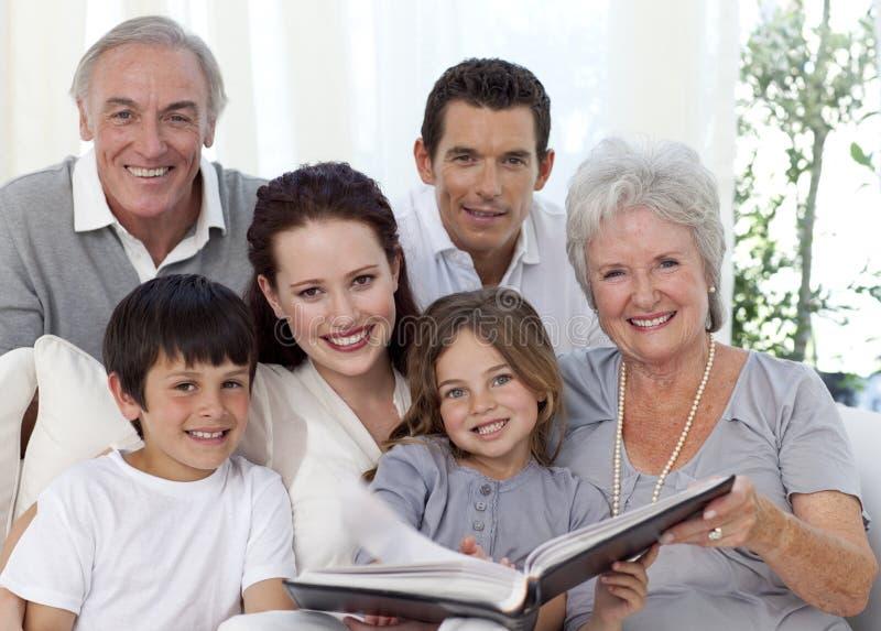 Lächelnde Familie, die ein Fotographienalbum betrachtet lizenzfreie stockfotografie
