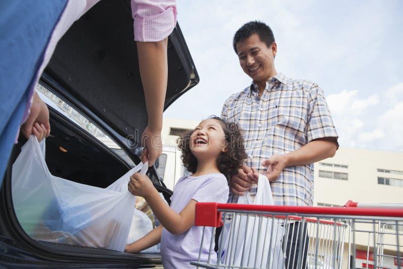 Lächelnde Familie, die Einkaufstaschen in das Auto, draußen spricht und setzt lizenzfreie stockbilder