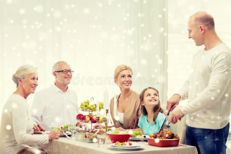Lächelnde Familie, die Feiertag zu Hause zu Abend isst stockfotos