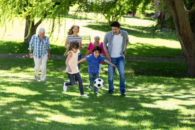 Lächelnde Familie, die Fußball spielt lizenzfreie stockfotografie