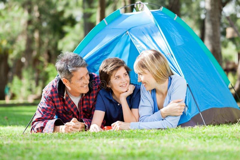 Lächelnde Familie, die im Park kampiert stockfotos
