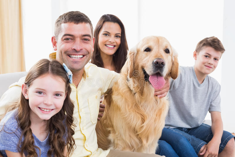 Lächelnde Familie, die mit golden retriever auf Sofa sitzt stockfoto