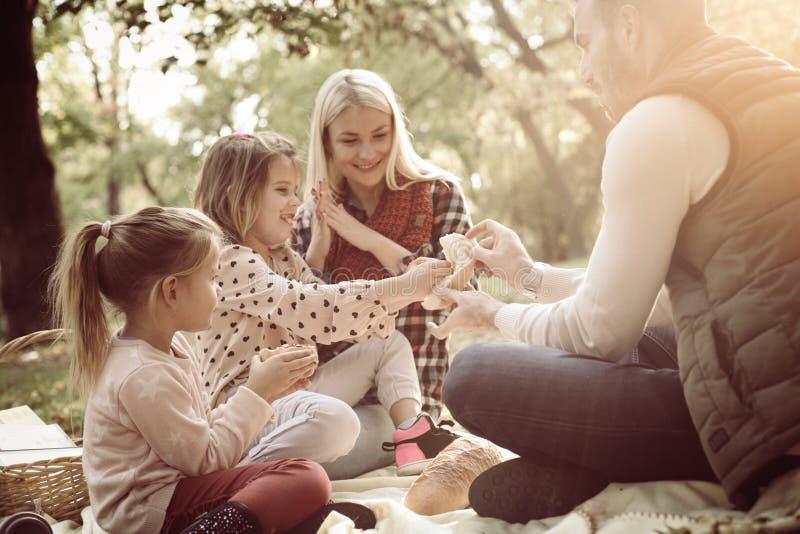 Lächelnde Familie, die Picknick zusammen im Park und in der Unterhaltung hat lizenzfreies stockbild