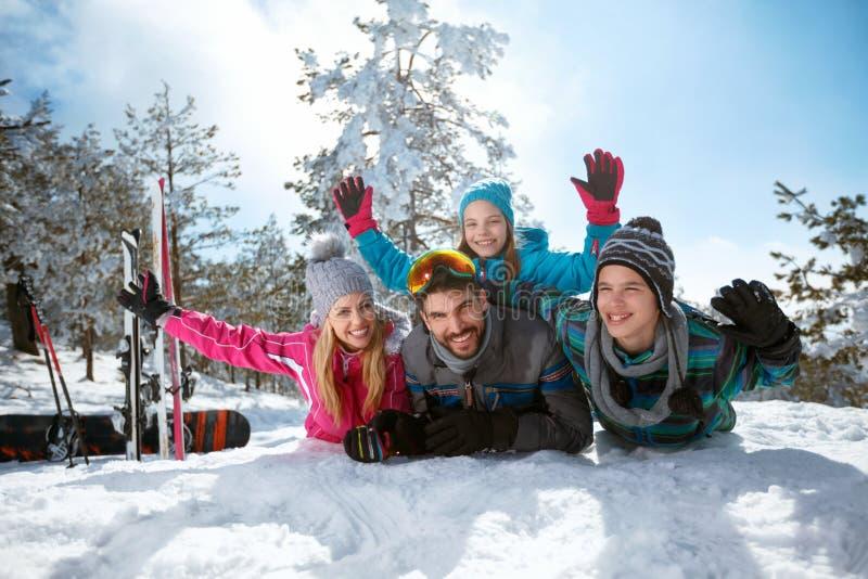 Lächelnde Familie, die Spaß auf frischem Schnee auf Winterferien hat stockfotografie